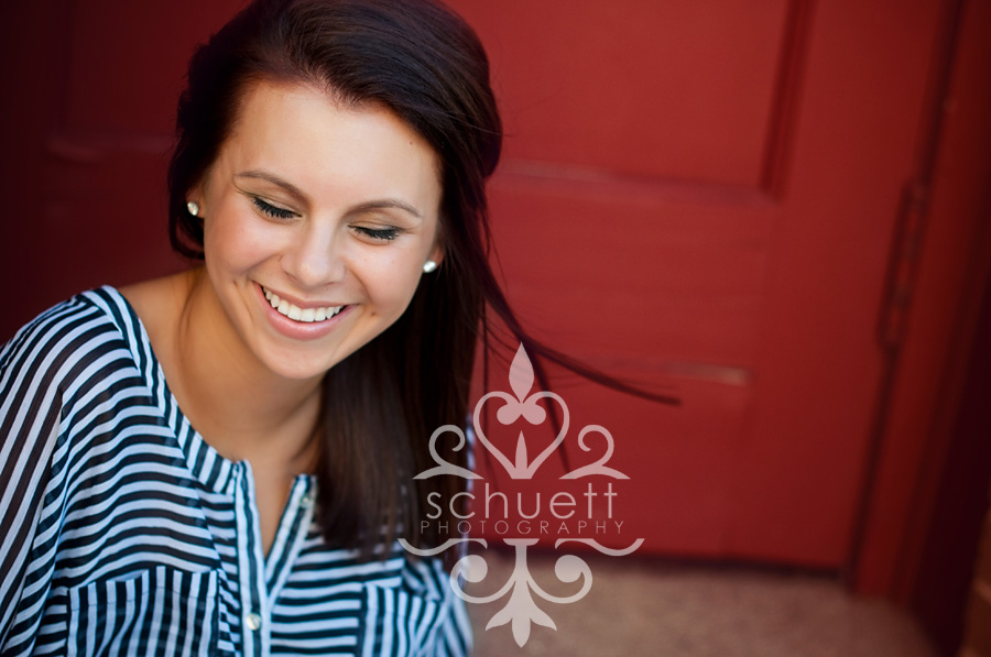 Senior picture with eyes closed in the summer breeze against a red door, stripes do look good for pictures