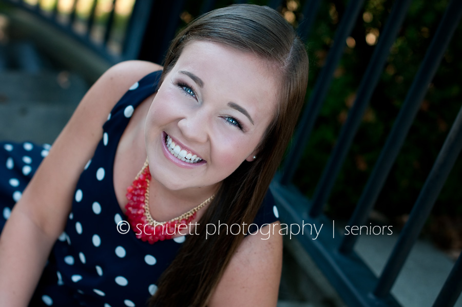 Girl senior smiling with a blue polkadot dress and coral necklace
