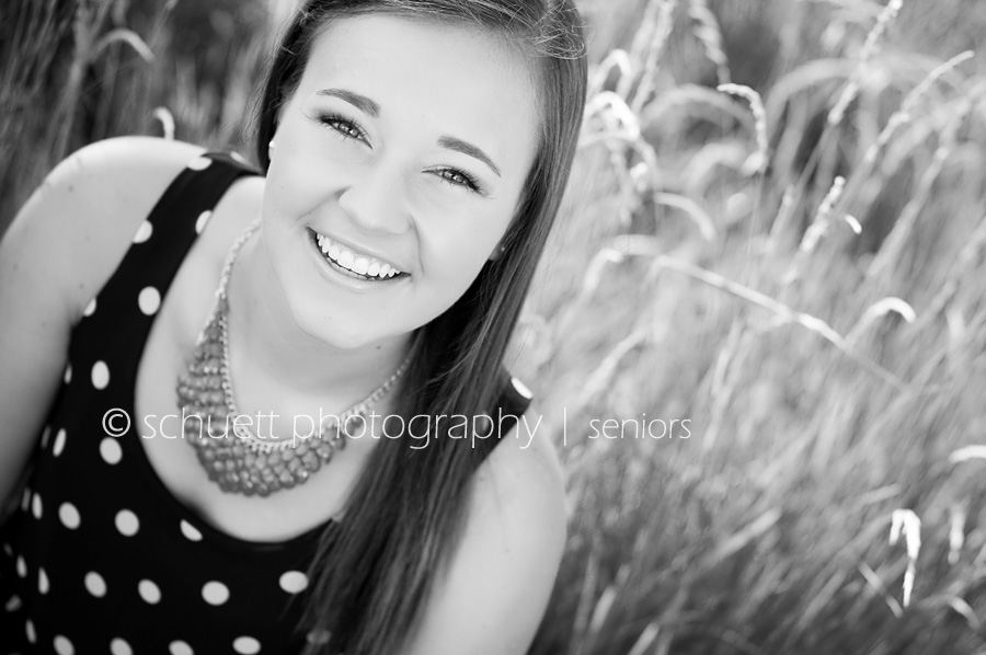 Black and white senior pictures with a polka dot dress and wispy grass in the background